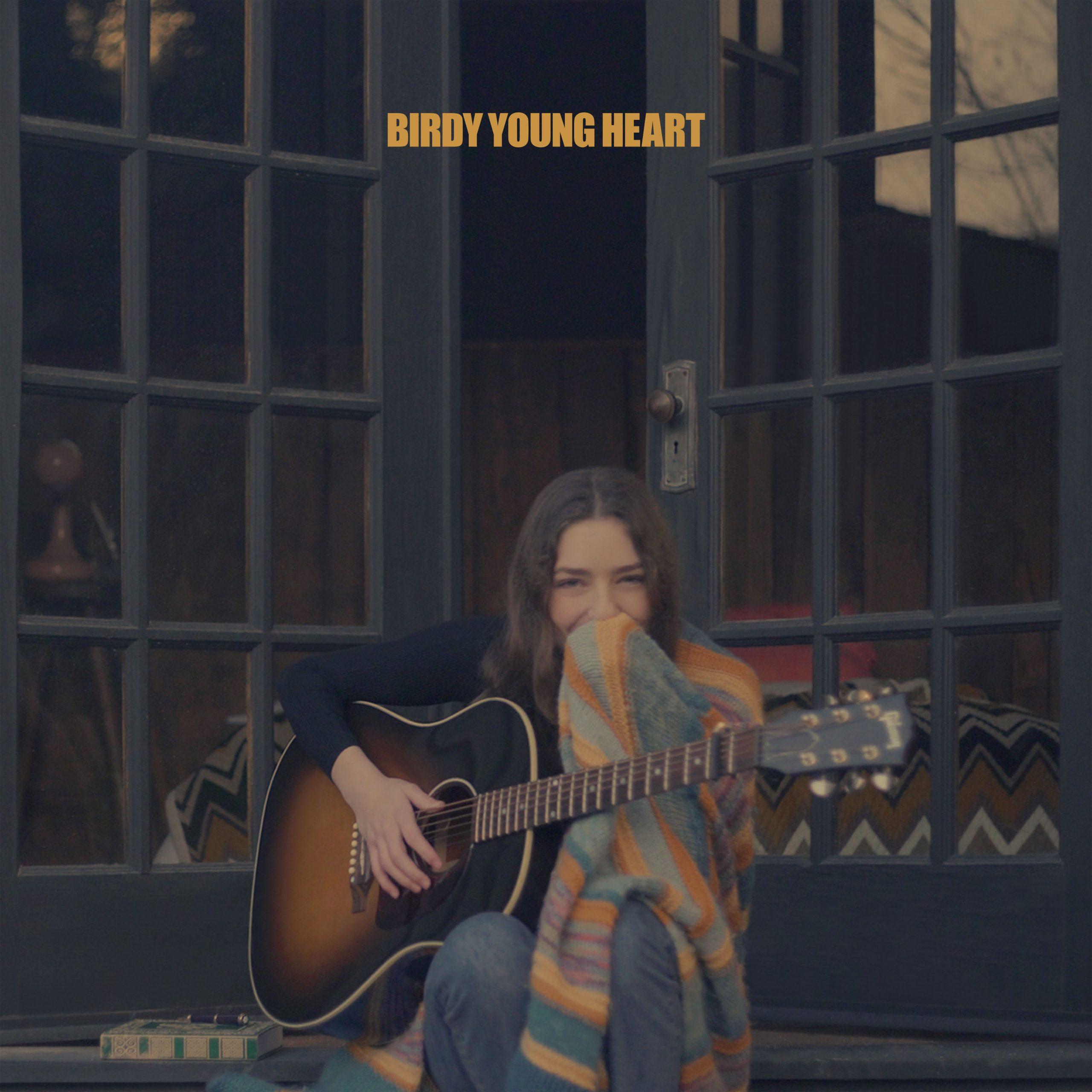Capa do CD Young Heart, de Birdy. Nela vemos a cantora, uma jovem branca de cabelos castanhos, sentada na frente de uma porta de vidro entreaberta. Ela segura um violão e um tecido.