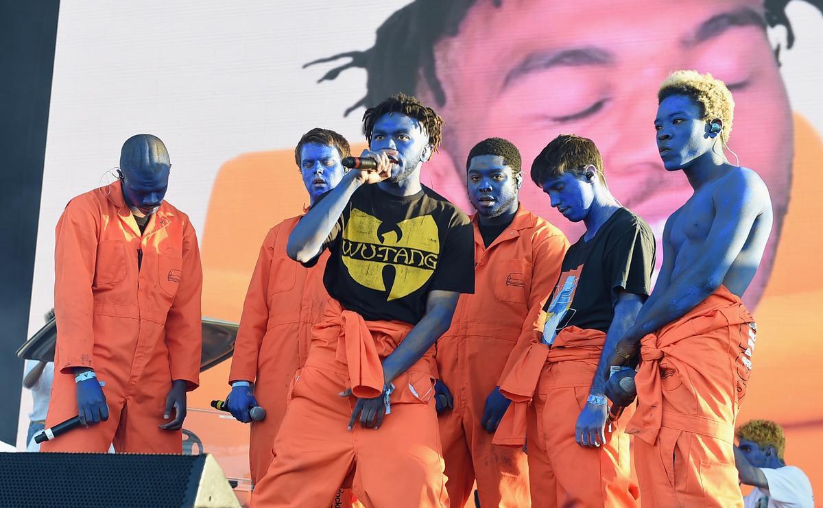 Fotografia colorida da banda BROCKHAMPTON. Eles estão em cima de um palco, enquanto apresentam um show. Primeiro, à esquerda, vemos Ameer Vann, um homem negro, de cavanhaque e cabelo raspado. Ele usa um macacão laranja, e sua pele está inteiramente pintada de azul. Ele está de cabeça abaixada, segurando seu microfone com os braços abaixados e colados ao corpo. Ao seu lado esquerdo, vemos JOBA, um homem branco, sem barba e cabelos loiros lisos em um corte curto. Ele usa um macacão laranja, e sua pele está inteiramente pintada em azul. Seus olhos estão fechados, enquanto segura seu microfone com o braço direito colado ao corpo. Ao seu lado esquerdo está Dom McLennon, um homem negro, sem barba e de cabelo raspad+o+. ele usa um macacão laranja, e sua pele está inteiramente pintada em azul. Ele olha para frente com os braços abaixados e colados ao corpo. Ao seu lado esquerdo, está Matt Champion, homem branco, sem barba e seus cabelos curtos e lisos da cor preta penteados para frente. Ele veste um macacão laranja, com a parte de cima presa em sua cintura pelas mangas, e uma camiseta preta de mangas curtas com uma estampa vermelha e azul no centro. Sua pele está inteiramente pintada em azul, e seus braços estão abaixados, colados ao corpo, enquanto ele olha para o chão de olhos fechados. Ao seu lado esquerdo, vemos Merlyn Wood, homem negro, sem barba, com cabelos crespos tingidos de loiro em um pequeno volume. Ele usa um macacão laranja, com a parte de cima presa em sua cintura pelas mangas, expondo seu peitoral. Ele olha para frente, com seu braço direito, que segura o microfone, abaixado e colado ao corpo e seu braço esquerdo o segurando pelo pulso. Por fim, vemos ao centro, à frente de todos, Kevin Abstract, homem negro, de barba feita e cabelos pretos, com as laterais raspadas e em curtos dreads no topo. Ele veste um macacão laranja, com a parte de cima presa em sua cintura pelas mangas, e uma camiseta preta de mangas curtas que estampa a logo do grupo de hip-hop Wu-Ta
