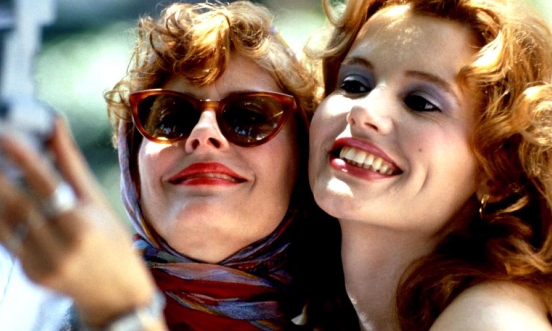 Cena do filme em que Geena Davis, uma jovem branca de cabelos claros e ondulados, e Susan Sarandon, uma jovem branca de cabelos ondulados, com óculos de sol e lenço, se juntam para tirar uma selfie.