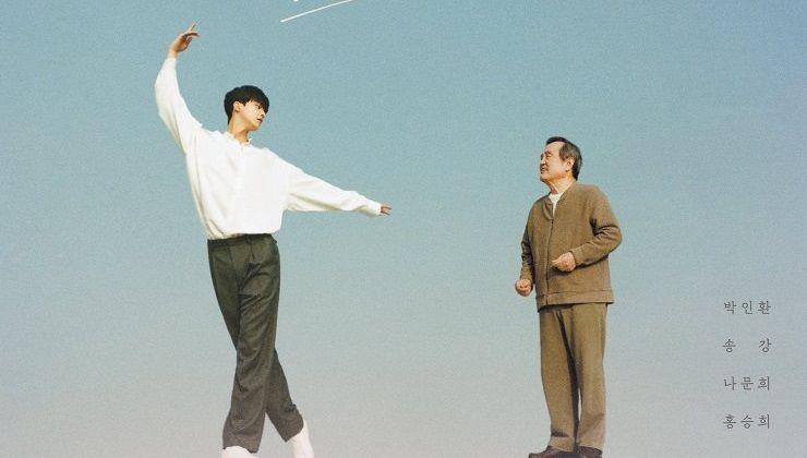 Foto Promocional do drama Navillera. Na imagem se vê à esquerda o ator Song Kang, que interpreta Lee Chae Rok. Ele usa uma blusa branca e calça social cinza enquanto faz uma posição de balé olhando para o lado. A direita está o ator Park In Hwan, que interpreta Shim Deok Chool. Ele usa um conjunto de moletom marrom claro e observa Song Kang fazendo posição de dança.