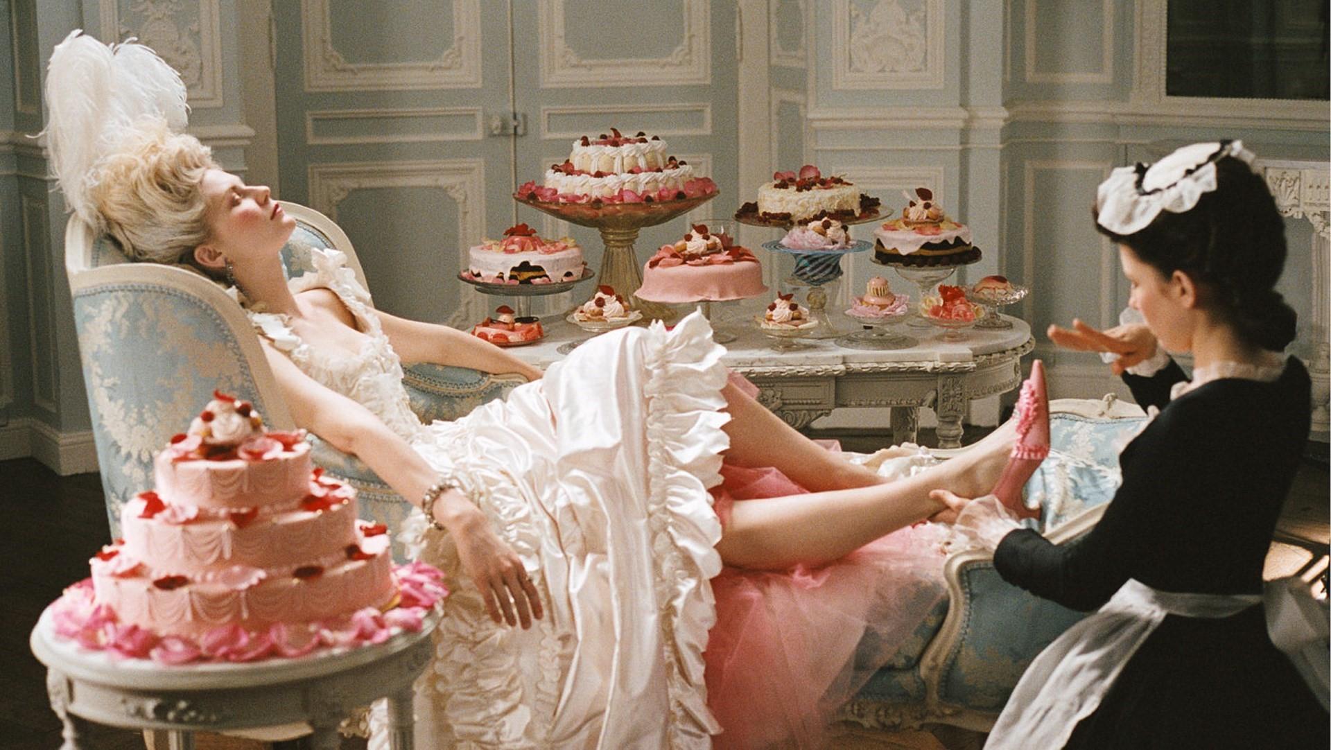 Cena da sequência de abertura de Maria Antonieta. Nela está Kirsten Dunst, que interpreta a rainha, uma mulher branca de cabelos loiros claros; usando um vestido branco de babados e uma pena branca como adorno na cabeça. Ela está deitada voltada para o lado direito, e uma mulher branca de cabelos pretos com um vestido preto, avental e chapéu branco está massageando seus pés. Elas estão cercadas por vários bolos.