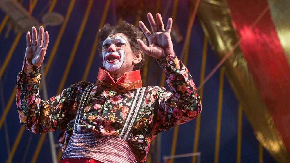Cena do filme O Auto da Boa Mentira. A imagem traz o personagem de Jackson Antunes caracterizado de palhaço, com gravata grande, roupas de cores fortes e maquiagens extravagantes.