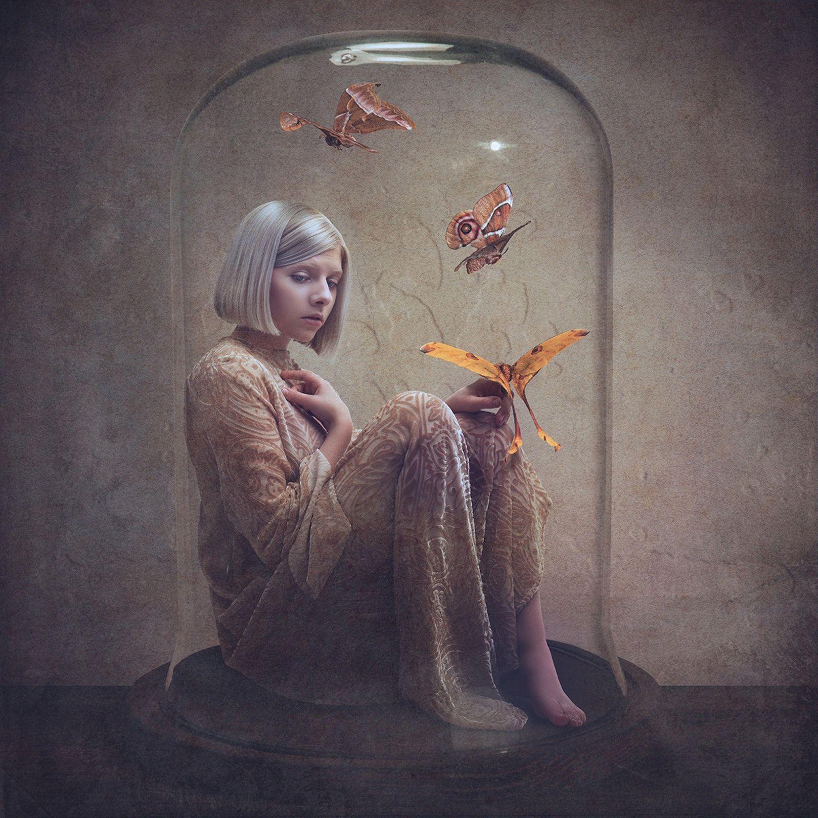 Fotografia do álbum All My Demons Greeting Me As A Friend, da cantora AURORA. A foto tem um fundo escuro com grande foco de iluminação ao centro, onde está a cantora, uma mulher branca de cabelos loiros e curtos, e olhos azuis. AURORA está vestindo um longo vestido bege com detalhes em marrom. Ela está sentada dentro de uma grande cúpula de vidro. E junto com ela estão três borboletas de tons branco, marrom, laranja e amarelo.