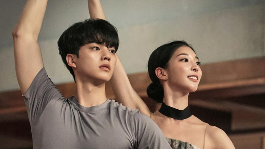 Na foto Lee Chae Rok faz posição de dança. Ele usa uma camiseta cinza e olha para a frente com o braço levantado. Atrás dele está posicionada outra bailarina com collant de balé e cabelo preso em um coque. Ela faz a mesma pose que ele. A imagem mostra apenas do peito para cima.