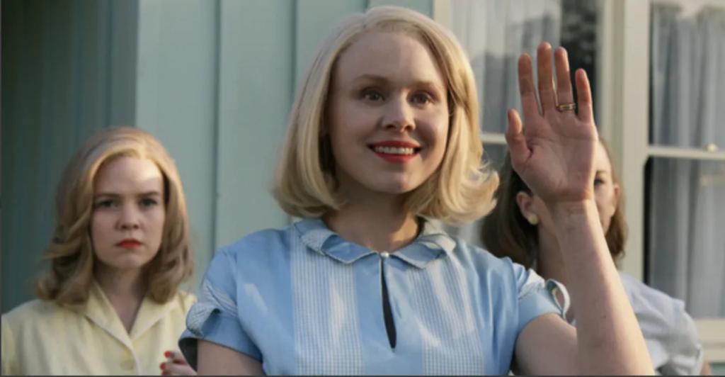 Cena da série Them. A imagem mostra a personagem Betty Wendell, interpretada por Allison Pill. Ela é uma mulher branca de cabelos loiros lisos na altura do ombro, está com um vestido azul e acena com a mão. Sua expressão facial é de um sorriso forçado, na mão levantada encontra-se um anel de casamento. Atrás dela estão duas mulheres, uma vestida de amarelo com uma expressão brava e outra vestida de branco, mas sua face está tapada pela mão de Betty. Atrás de todas está uma parede de tom claro e uma janela de vidro.
