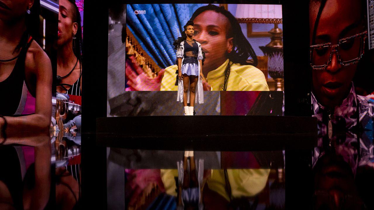 Cena do documentário. Na imagem, Karol está em pé em um palco reagindo à diversos telões que a cerca dos lados e atrás dela, reproduzindo cenas suas no reality Big Brother Brasil.