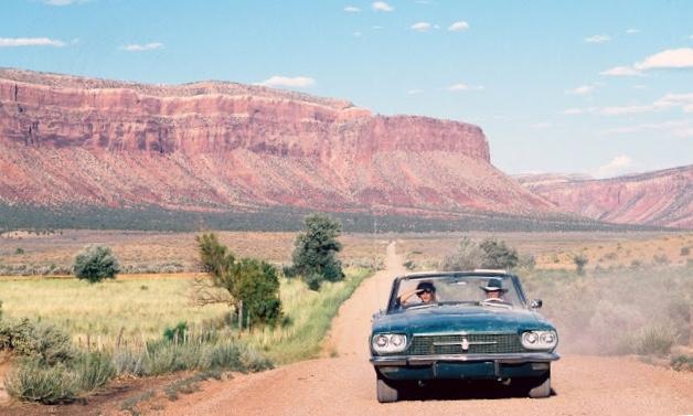 Cena do filme em que Thelma e Louise cruzam o deserto dentro de um carro conversível azul. A estrada é de terra, nos cantos está a vegetação baixa típica de clima desértico e uma montanha toma conta do fundo da imagem.