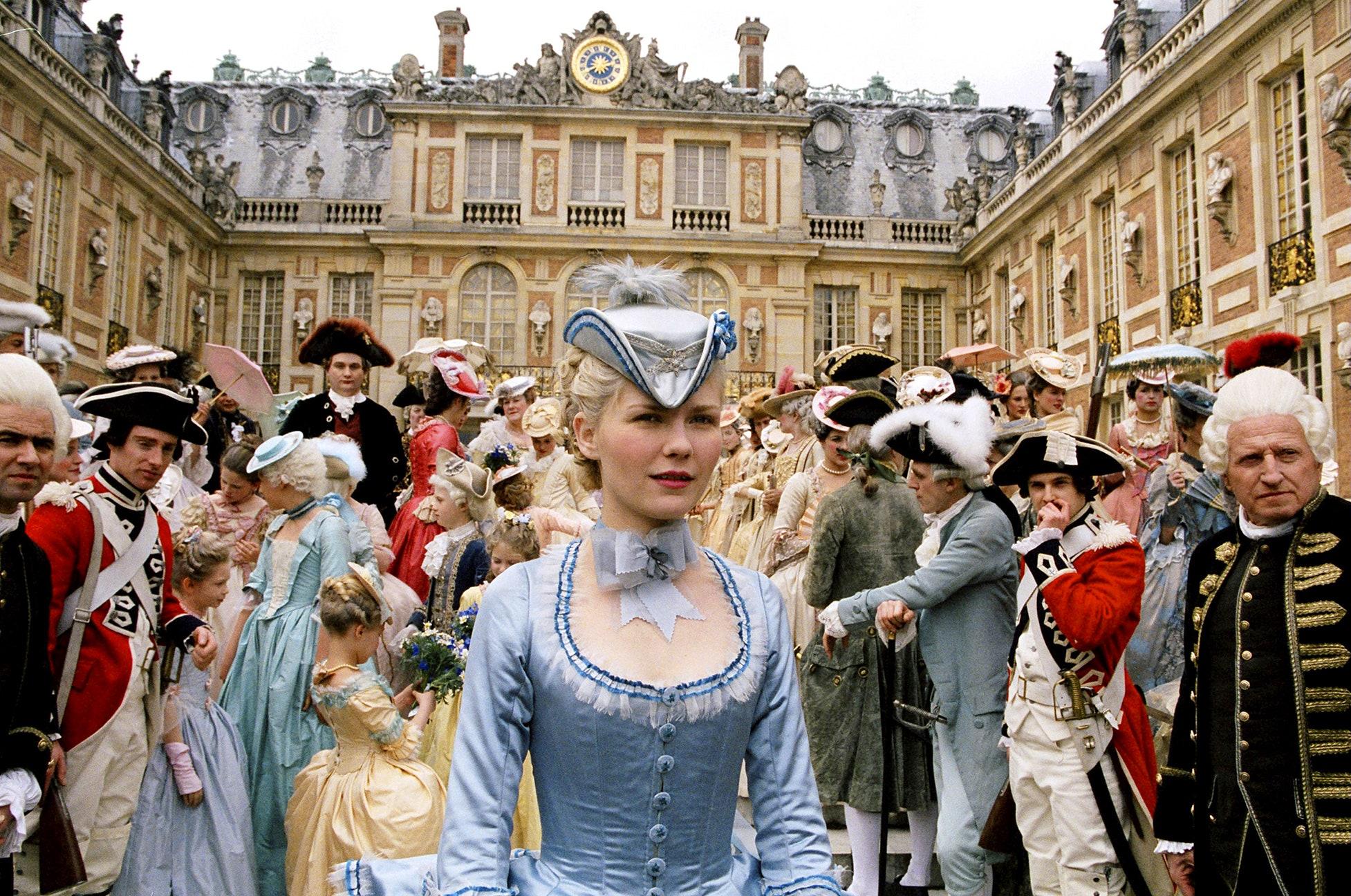 Cena do momento em que Maria Antonieta chega a Versalhes. Ela usa um traje azul claro, que contrasta com as roupas majoritariamente escuras da multidão que a cerca. Todos estão fora do palácio, cercados pela construção como se estivessem em um pátio.
