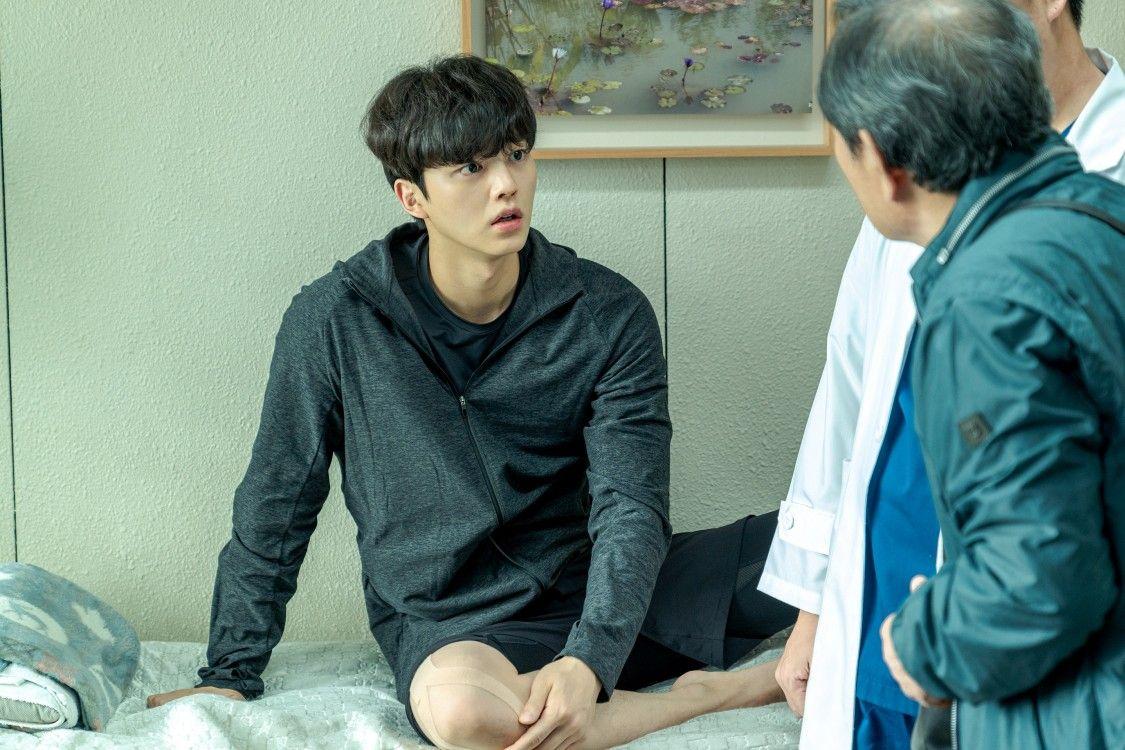 Na fotografia Chae Rok usa casaco cinza e bermuda preta. Ele está deitado em uma maca de clínica médica. No primeiro plano, Deok Chool o observa de costas para a câmera e usando um casaco verde. Entre os dois é possível ver um torso de médico usando jaleco.