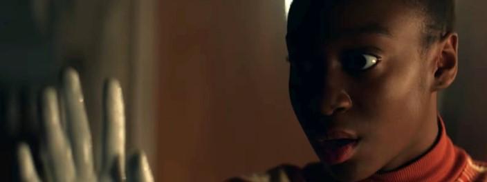 Cena da série Them. A imagem mostra a personagem de Ruby Emory, interpretada por Shahadi Wright Joseph. Ela é uma jovem negra de cabelos presos e olha espantada e fixamente para sua mão que está repleta de tinta branca. Ao fundo, o ambiente onde ela se encontra aparece desfocado. Ela veste uma roupa de gola alta com tons laranjas e amarelos.