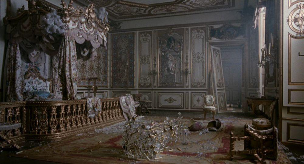 Cena do filme Maria Antonieta. Mostra um dos quartos do palácio totalmente destruído pelos revoltosos. Há um lustre de cristal despedaçado no chão, portas quebradas e mobílias reviradas. A imagem possui um tom acinzentado.