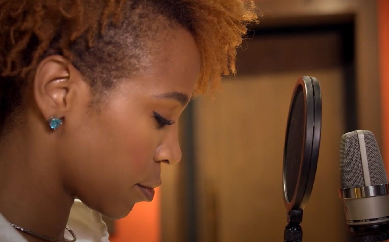 Cena do documentário. Na imagem, Karol está num estúdio de gravação. A única parte em evidência é o seu rosto em perfil. Na frente, um microfone. Karol está de olhos fechados, prestes a cantar.