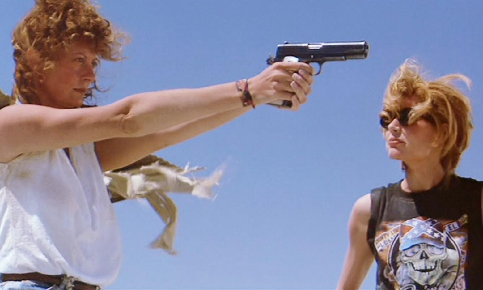 Cena do filme em que Susan Sarandon, a esquerda, aparece usando uma camiseta branca e apontando uma arma. A direita está Geena Davis, que usa uma camiseta preta com o desenho de uma caveira e óculos de sol. O fundo é o céu azul.