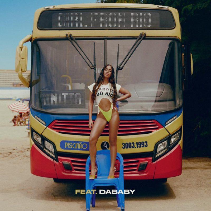 """otografia da capa do single Girl From Rio, da cantora Anitta. No centro está a cantora, uma mulher branca de cabelos castanhos e longos. Ela veste um maiô verde e uma blusa branca com o escrito """"Garota do Rio"""". A cantora está em pé, em cima de uma cadeira azul, em frente a um ônibus, que na parte superior está escrito """"Girl From Rio"""". O veículo está parado em uma praia no Rio de Janeiro. Na parte inferior da imagem, ao centro está escrito 'FEAT. DABAY', numa fonte em caixa alta, negrito e colorida em amarelo."""