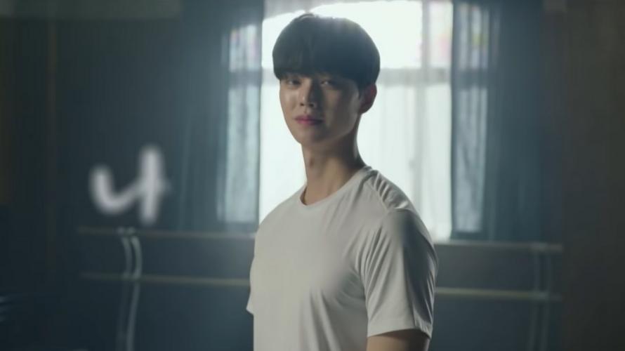 Na imagem Chae Rok olha para a frente com um sorriso no rosto. Ele usa uma camiseta branca simples e está em uma sala de treinamento com uma janela e cortinas atrás.