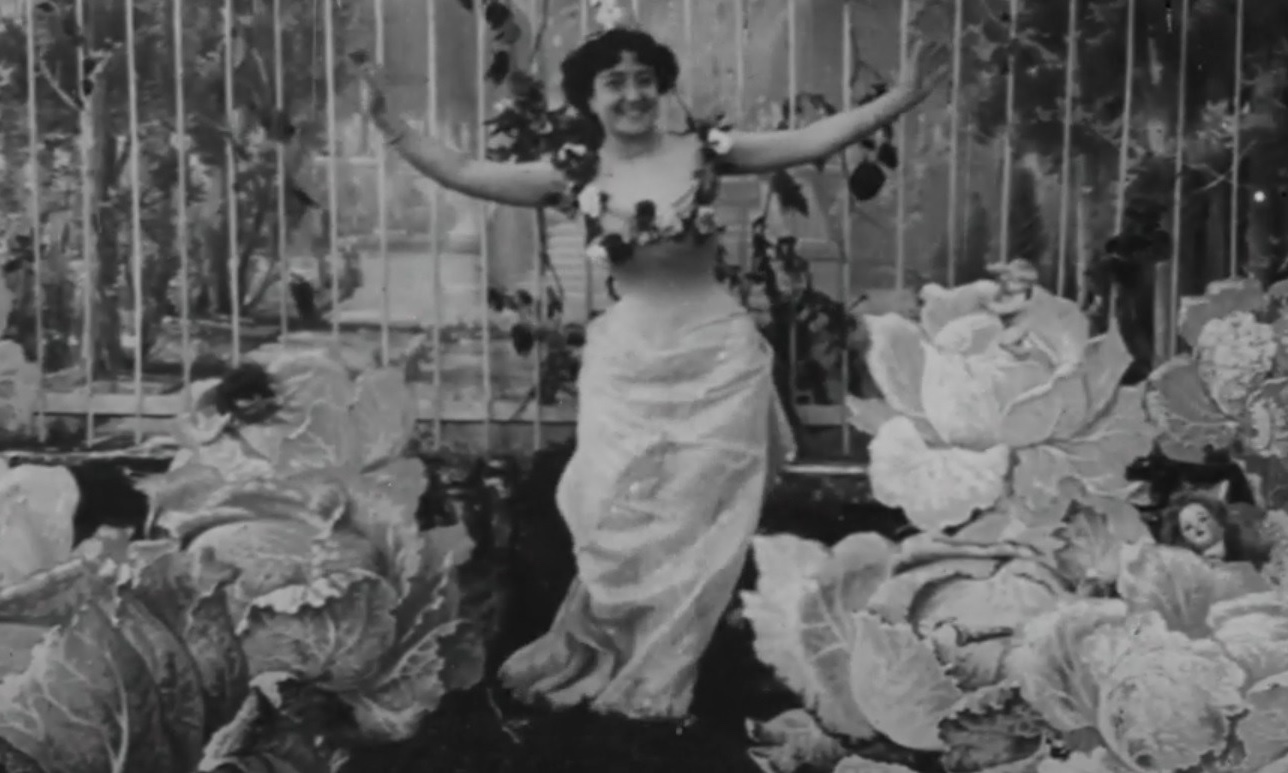 Cena branco e preta do curta A Fada do Repolho, em que Alice Guy-Blaché aparece ao centro sorrindo, com cabelo curto preto, um vestido longo branco e os braços erguidos. Ao seu lado estão vários repolhos fictícios grandes e ao fundo está uma grade.