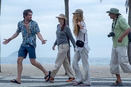 Cena do filme O Auto da Boa Mentira. Caminham pelo calçadão da praia em sentido esquerdo, dois homens e duas mulheres utilizando roupas claras e trajes adequados para o calor, como chapéus e chinelos.