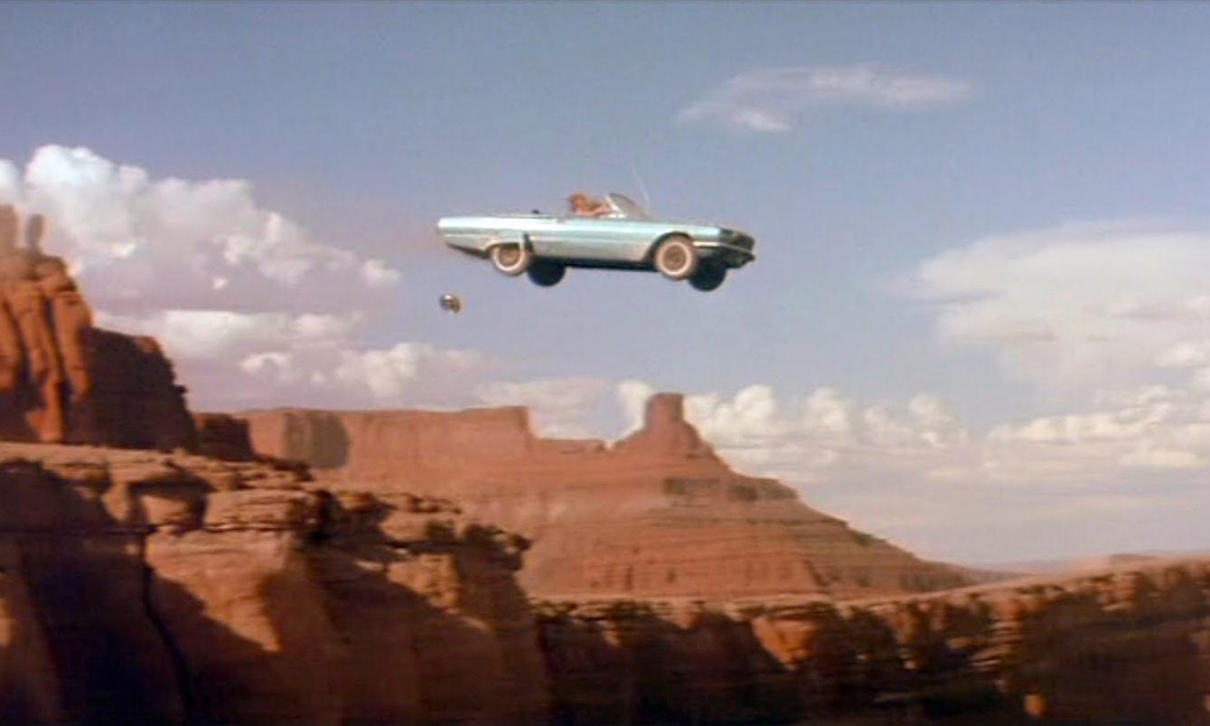Cena do filme em que um carro azul conversível sobrevoa o Grand Canyon. A metade para baixo da imagem é composta por rochedos desérticos e a parte superior é o céu azul com poucas nuvens dispersas.