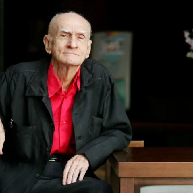 A imagem mostra o escritor Ariano Suassuna, homem branco, idoso, de cabelo e sobrancelhas grisalhas, vestindo uma camiseta vermelha e uma jaqueta preta por cima.