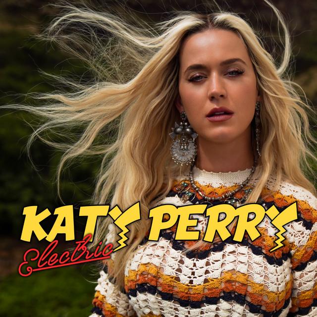 Capa do single Electric, de Katy Perry. Sobre uma paisagem verde, Katy Perry aparece do tronco para cima. Ela veste um casaco de crochê com linhas coloridas em branco, amarelo, vermelho e preto. Ela usa grandes brincos prateados em desenho circular e um colar prata. Katy é uma mulher branca de cabelos loiros e longos que balançam com o vento. Sua expressão é serena. Uma tipografia amarela revela o nome 'Katy Perry' e, abaixo, 'Electric' em vermelho.