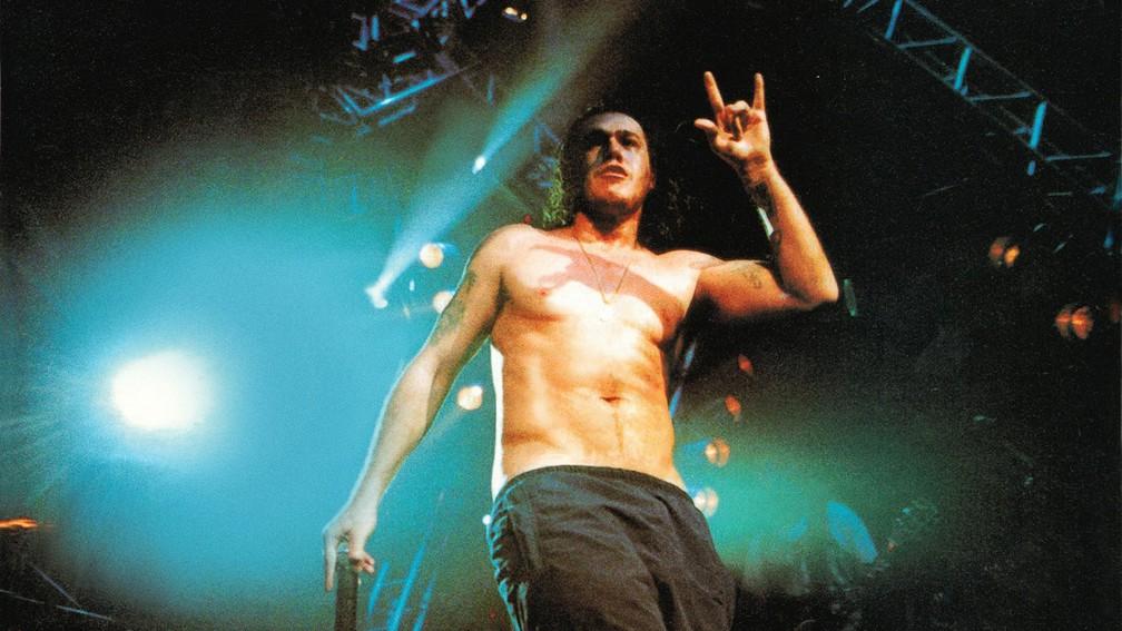 Chorão, um homem branco e de cabelos castanhos na altura do ombro está em um palco, usando uma calça preta, com o microfone na mão, sem camisa e com luzes azuis o iluminando. Ele tem algumas tatuagens no braço e está fazendo o gesto do rock.