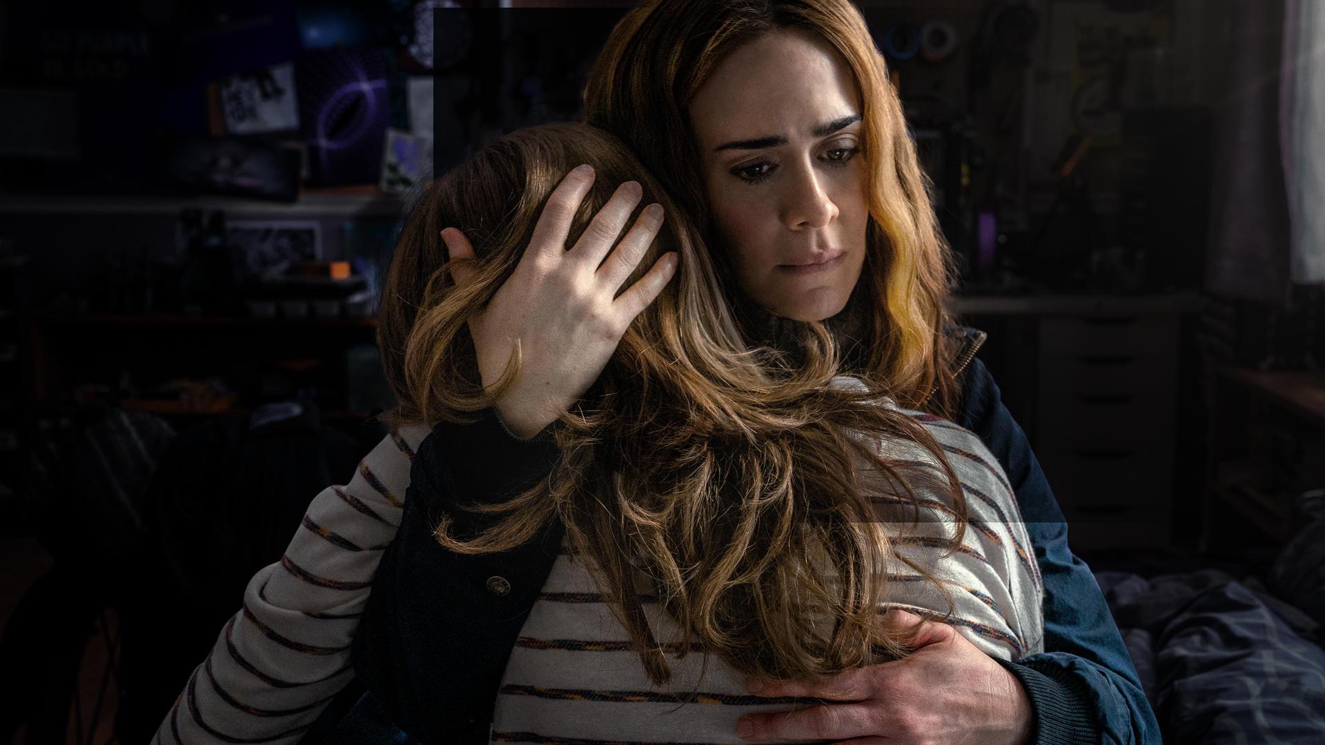 Cena do filme Fuja. Vemos a atriz Sarah Paulson, uma mulher branca adulta, abraçando sua filha interpretado por Kiera Allen. Sarah está de frente, olhando para baixo, e apoia sua mão direita na cabeça da jovem, que está com o rosto escondido no ombro da atriz.