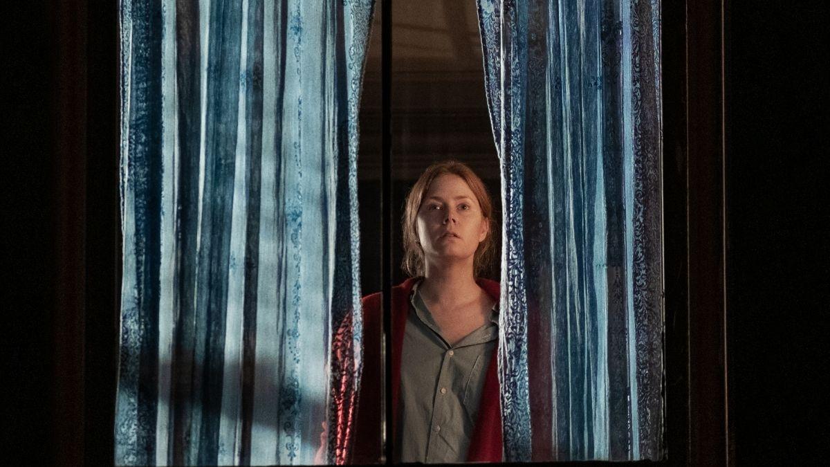 Cena do filme A Mulher na Janela. Nela, vemos Amy Adams, branca, ruiva, de camiseta cinza e jaqueta vermelha, olhando pela janela, com duas cortinas dividindo a imagem e ela no centro, com uma expressão aflita.