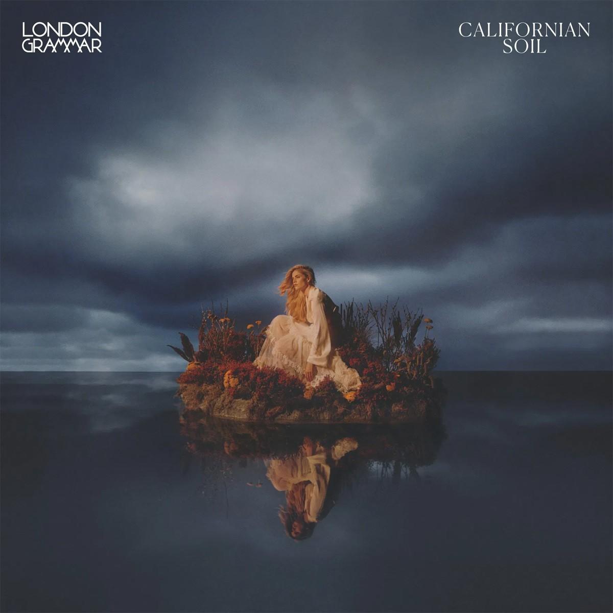 Capa do CD Californian Soil, da banda London Grammar. Na capa, vemos uma mulher loira sentada em pedras, acima do mar. No canto superior esquerdo, está escrito London Grammar, em fonte branca, e no canto superior direito, Californian Soil.