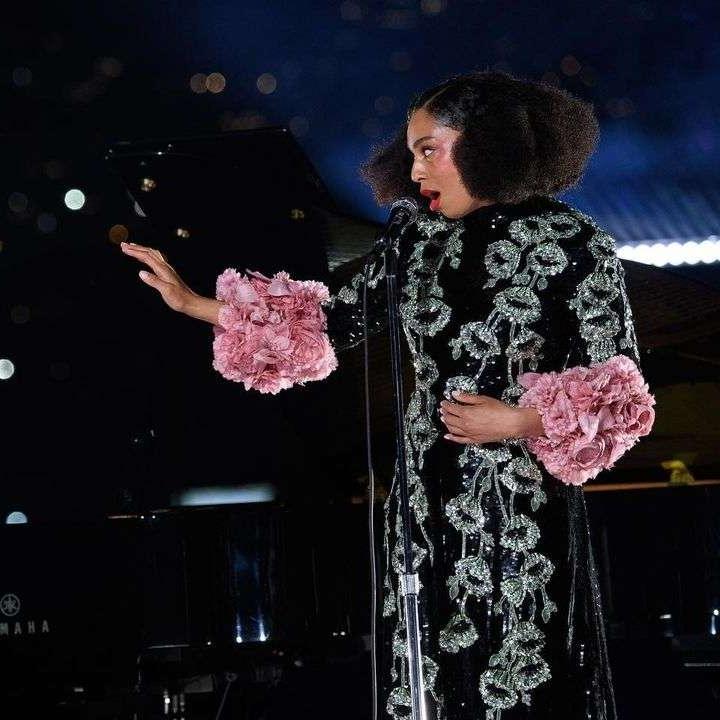 Foto de Celeste. A mulher negra, de cabelos soltos, usa um vestido preto, com detalhes em verde, e uma manga rosa esvoaçante. Ela canta no microfone à sua frente, com a mão esquerda levantada e a direita encostada em sua barriga. No fundo é possível ver um piano preto, e luzes que se destacam na escuridão da noite.