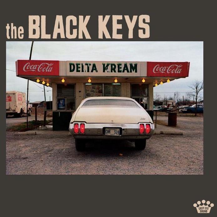 """Capa do disco Delta Kream, de The Black Keys. A capa é composta por uma fotografia posicionada ao centro sob um fundo marrom médio e embaixo do nome da dupla que assina o álbum, escrito numa cor creme e alinhada à direita. Neste escrito, 'the' está em letras minúsculas e num tamanho menor e 'BLACK KEYS"""" está em caixa alta, num tamanho maior. A fotografia do centro apresenta, a traseira de um carro antigo parado de frente para um estabelecimento. O lugar tem uma placa de metal que contorna o telhado, onde está escrito ao centro DELTA KREAM numa fonte preta em caixa alta sob um fundo branco, ao centro. Nas laterais, existe o logo da Coca-Cola- repetido no lado esquerdo e no lado direito. O estabelecimento é pequeno e no ângulo em que está fotografado apresenta três janelas, uma ao centro e duas nas laterais. Elas são teladas e possuem cartazes colados. Ao redor do telhado, existe um fio de luzinhas redondas amarelas e bancos de madeira. O carro, que está estacionado à frente, é num amarelo claro. Atrás do estabelecimento existe uma rua, com vários carros estacionados, e ainda atrás, do lado esquerdo, existe um caminhão pequeno bege. O céu está nublado, num tom cinza azulado."""
