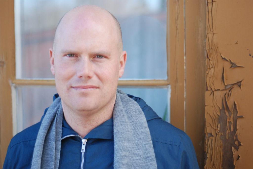 Fotografia de M.T. Edvardsson. O sueco está enquadrado na direita da imagem, na região do peito para cima. Ele é um homem branco, de meia idade e careca. M.T. usa uma jaqueta azul e um cachecol cinza.