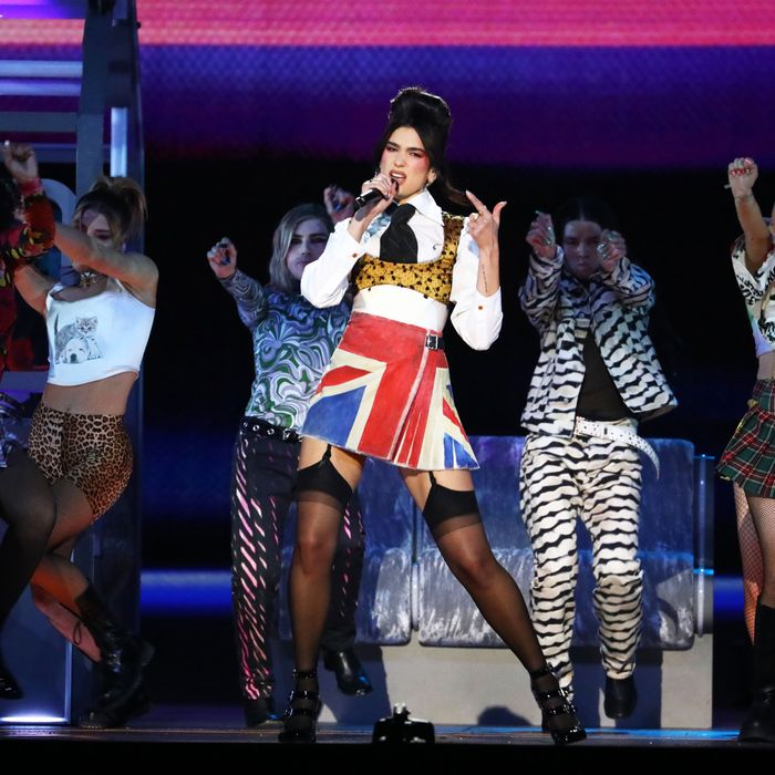 Foto de Dua Lipa. A cantora branca e magra tem seus cabelos pretos presos em um coque alto e volumoso. Ela veste uma saia com a bandeira do Reino Unido, uma camisa branca, um top amarelo por cima e uma gravata preta. No pé usa um salto preto com uma meia calça preta. A mulher está cantando, segurando um microfone na mão direita. No fundo, quatro dançarinos a acompanham, fazendo um paço com as mãos para frente. Atrás deles, um painel rosa e roxo, e um banco de metrô.