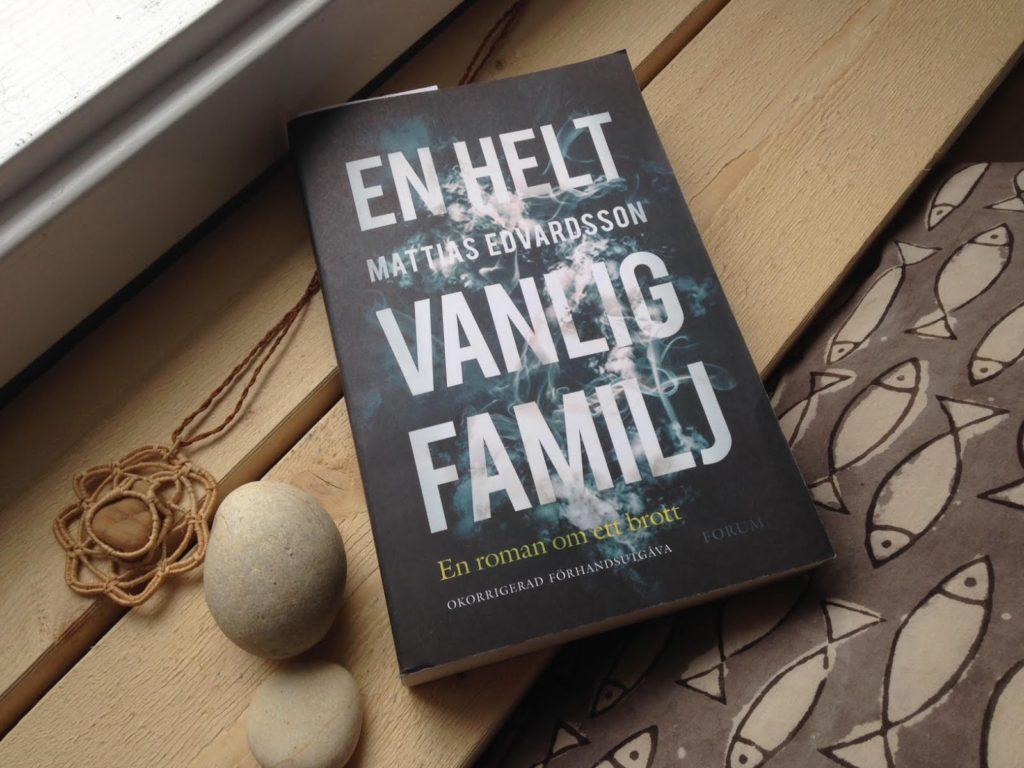 Fotografia do livro En Helt Vanlig Familj. O livro está no centro da imagem, fotografado de cima para baixo. A capa contém o nome do livro em letras brancas e grandes, formando um bloco de texto. O fundo da capa é preto com símbolos de fumaça. Ele está apoiado em um batente de madeira.