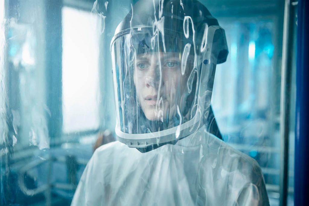 Cena do filme Oxigênio. Na imagem, Elizabeth está em frente a uma cortina de plástico com uma máscara protetora hospitalar cobrindo sua cabeça. Vivida por Mélanie Laurent, ela é uma mulher branca de olhos azuis e cabelos loiros, a personagem veste uma roupa branca e está em um hospital.