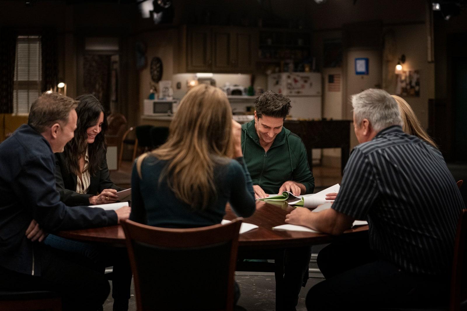 Cena do episódio especial Friends: The Reunion. Nela, vemos os 6 atores sentados ao redor de uma mesa de madeira, com roteiros de papel sulfite na mão, rindo e se olhando.