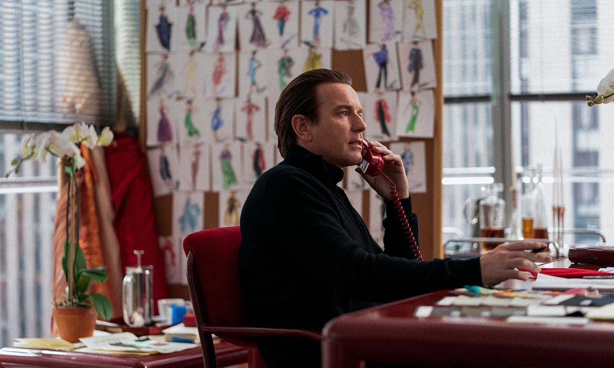 Imagem da série Halston. A imagem mostra o protagonista, Roy Halston, intepretado por Ewan McGregor, sentado em sua mesa de trabalho enquanto fala ao telefone. Ele é um homem branco, de cabelos castanhos lisos, e veste uma blusa preta de gola alta. A mesa e a cadeira são vermelhas, e atrás de Halston, ao fundo, pode-se observar desenhos de vestidos colados na parede entre duas janelas grandes que mostram uma paisagem de prédios.