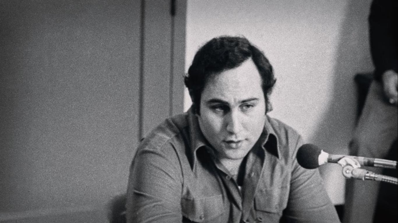 Foto em preto e branco de David Berkowitz. David é um homem branco e jovem de cabelos escuros e curtos. Ele usa uma camisa de mangas compridas. David está sentado, podemos vê-los do peito para cima à direita da imagem. Na sua frente, à direita, está um microfone posicionado em sua direção.