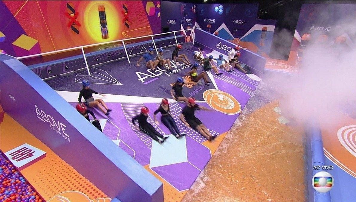 Cena do Big Brother Brasil 21. A imagem mostra os brothers que participaram da prova da Above descendo a rampa de largada em direção a uma piscina de água. Eles vestem capacetes.