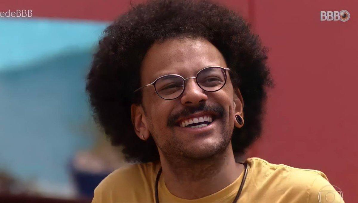 Cena do Big Brother Brasil 21. João Luiz, vestindo uma camiseta laranja e óculos, sorri.