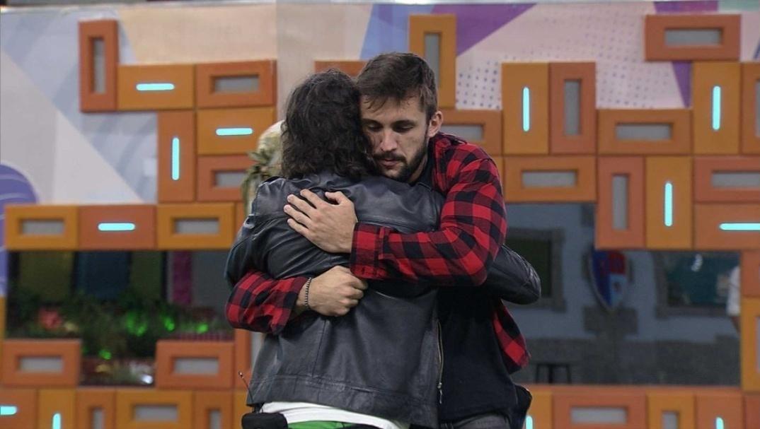 Cena do Big Brother Brasil. Arthur e Fiuk se abraçam no jardim. Fiuk está de costas e Arthur de frente para a câmera.