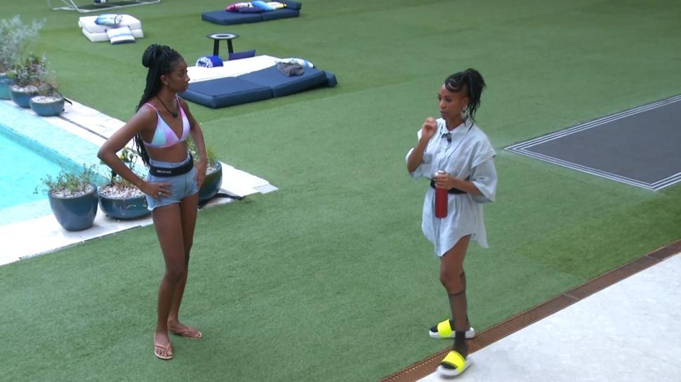 Cena do Big Brother Brasil 21. Camilla e Karol Conká olham uma para a outra no jardim. A câmera mostra as duas de corpo inteiro.
