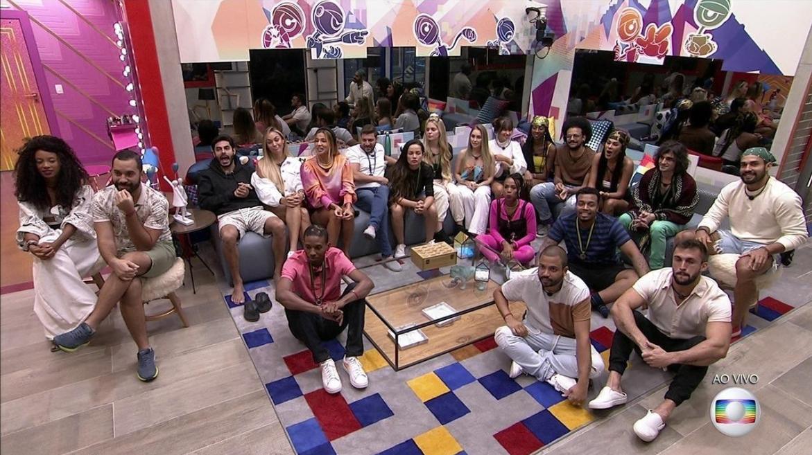 Cena do Big Brother Brasil 21. Todos os participantes estão na sala, alguns sentados no sofá e outros sentados no chão. A decoração é colorida, há uma mesa de centro e eles olham em direção ao telão, posicionado embaixo da câmera.