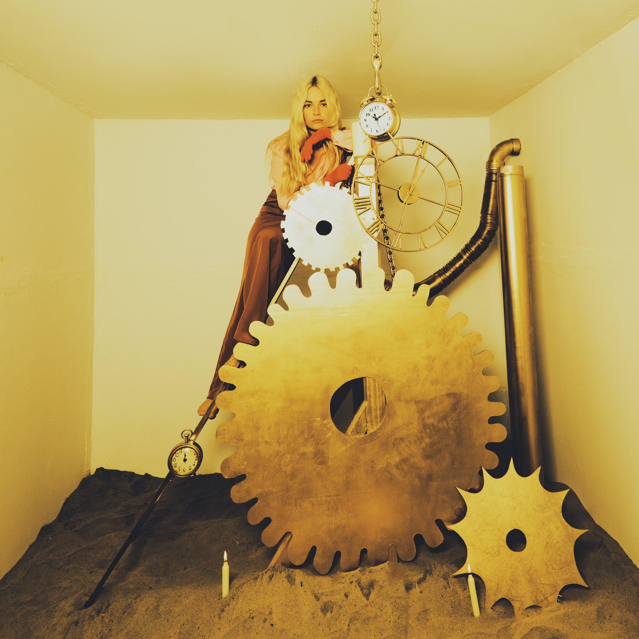 A imagem mostra a cantora Ashe, com os cabelos loiros soltos, calça social marrom, camisa amarela e luvas laranjas em cima de algumas engrenagens de um relógio. O fundo da imagem é branco e o chão é feito de areia, com duas velas acesas. A imagem tem uma tonalidade amarelada e envelhecida.