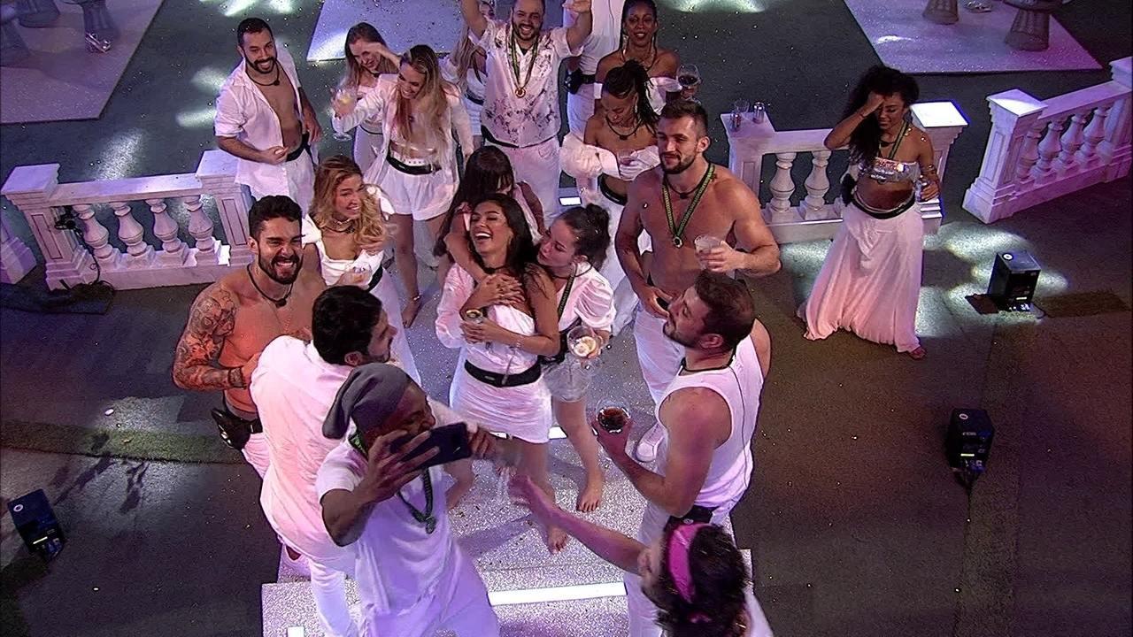 Cena do Big Brother Brasil 21. Vários participantes estão se divertindo na Festa Réveillon, vestidos de branco.