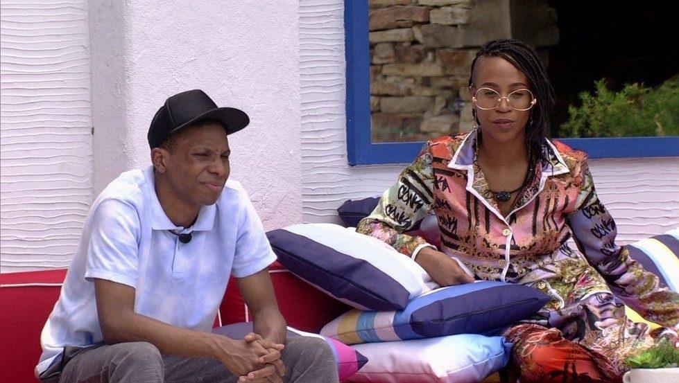 Cena do Big Brother Brasil 21. Lucas e Karol Conká conversam em um sofá na area externa da casa.