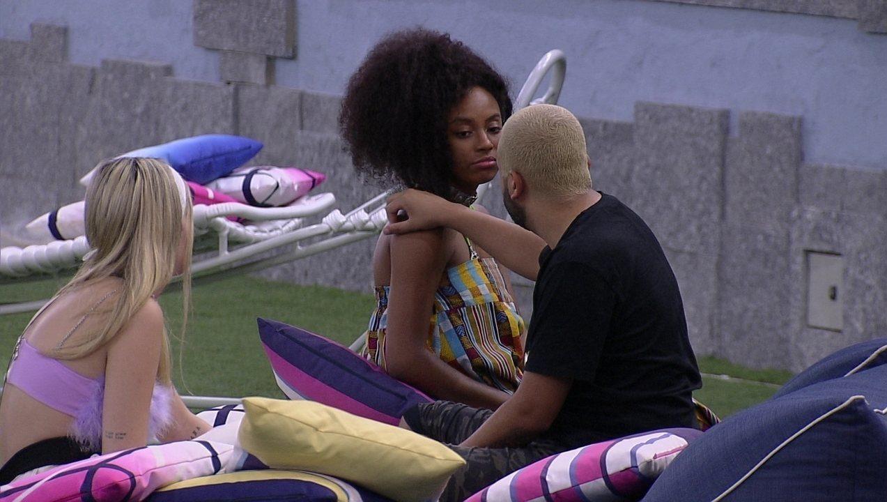 Cena do Big Brother Brasil 21. Lumena e Projota conversam no lado de fora da casa, em um dos colchões externos. Projota está de costas com a mão no ombro de Lumena, que olha para seu rosto.