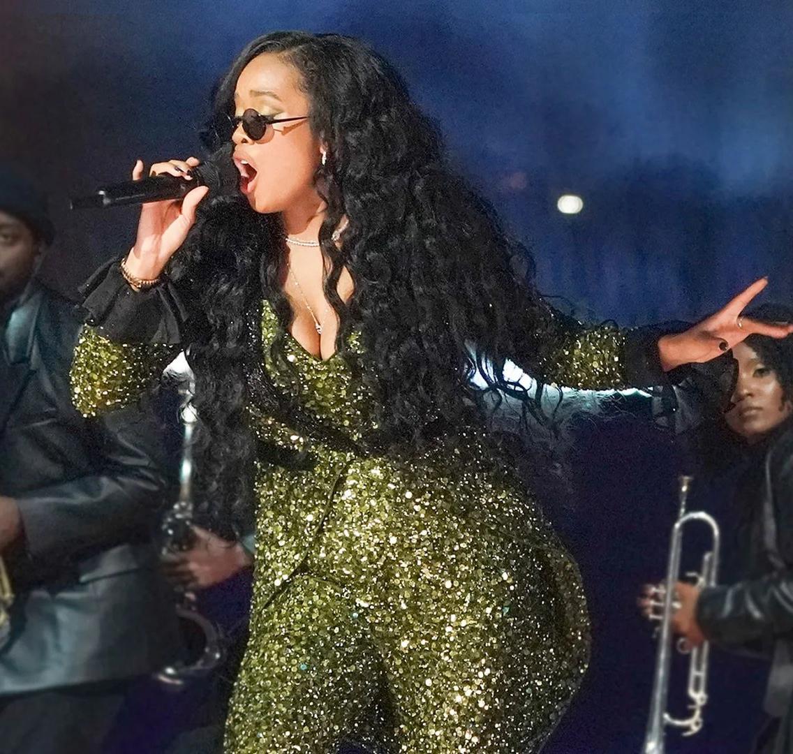 Foto quadrada da cantora H.E.R. Ela é uma mulher negra, de cabelos preto, longo e ondulado. Ela usa um macacão longo e dourado brilhante. Usa também óculos escuro redondo. Em sua mão direita há um microfone. O fundo é azul e vemos mais pessoas da banda.