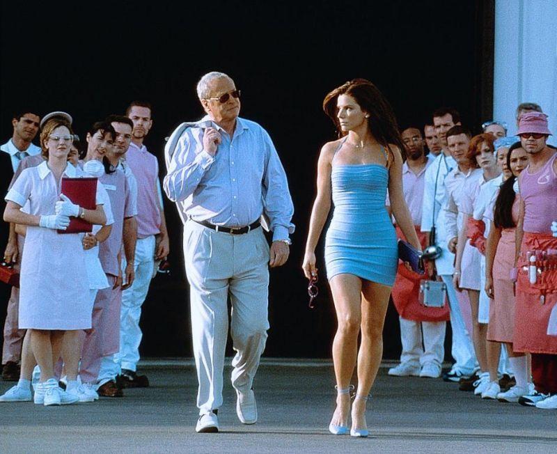 Cena do filme Miss Simpatia. Nela vemos Sandra Bullock, uma mulher jovem branca e com cabelo liso médio castanho. Ela veste um vestido azul claro, um salto azul escuro e segura um óculos de sol na mão direita e uma bolsa azul na mão esquerda. O ator Michael Caine caminho ao seu lado. Ele é um homem branco idoso. Ele usa óculos de sol e veste uma camisa social azul claro e uma calça social bege. Ele segura um paletó bege sobre o ombro. Os dois estão saindo de um hangar e ao lado deles há várias pessoas observando eles.