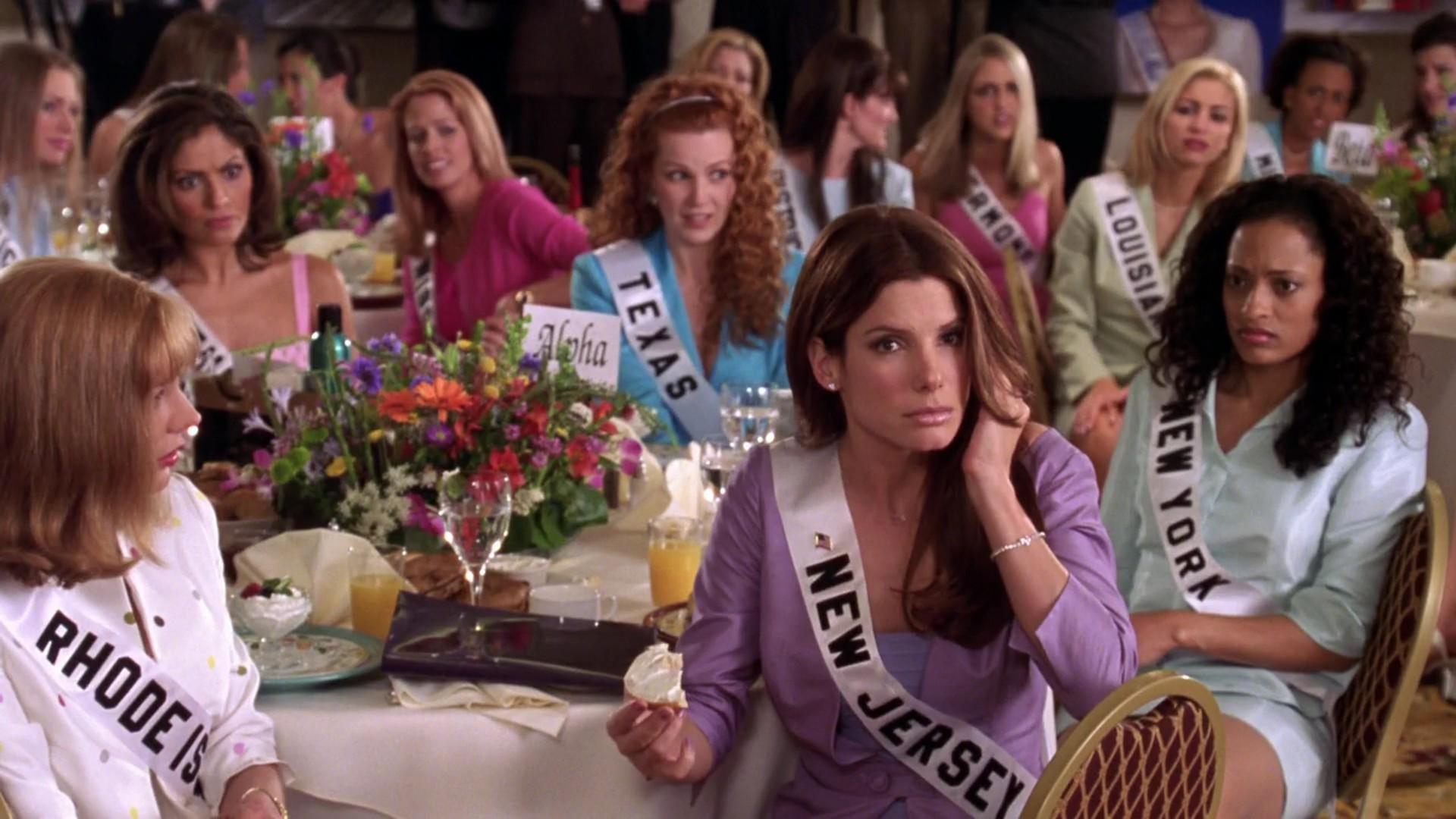 Cena do filme Miss Simpatia. Na imagem vemos uma sala com diversas mulheres sentadas em volta das mesas. As mesas possuem toalhas bege, decorações e alimentos em cima delas. Todas as mulheres possuem uma faixa que direciona o estado que representa na competição. Todas elas estão olhando perplexas para Sandra Bullock, uma mulher jovem branca e com cabelo liso médio castanho. Ela veste um terno lilás e usa uma faixa escrito New Jersey.