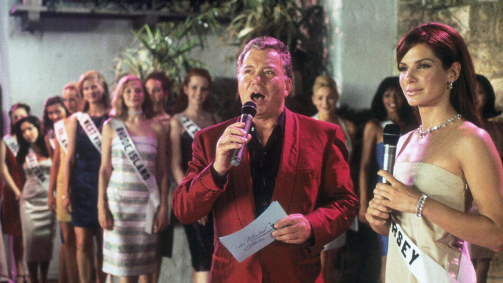 Cena do filme Miss Simpatia. Na imagem vemos a atriz Sandra Bullock e o ator William Shatner. A mulher veste um vestido longo bege brilhante e usa uma faixa escrito New Jersey e um colar. Ela segura um microfone e olha para o horizonte. Ao seu lado, William Shatner, um homem branco idoso veste um paletó vinho e uma camisa social preta. Ele segura um microfone e um papel. Atrás deles, há várias mulheres usando vestidos longos de festa.